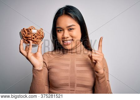 Young asian girl holding bowl with baked german pretzels over isolated white background surprised with an idea or question pointing finger with happy face, number one