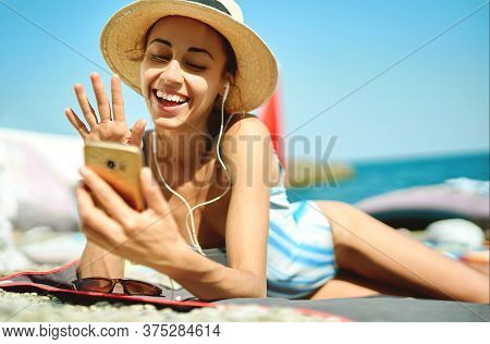 Young Woman In Hat Laughting And Talking On Video Call On Smartphone, Chatting With Friends At Beach