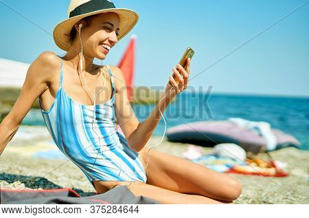 Joyful Smiling Girl In Hat Lying On Beach At Summer Holidays, Holding Smartphone