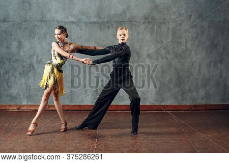 Young Couple Sport Dancers Dancing In Ballroom Dance Cha-cha-cha.