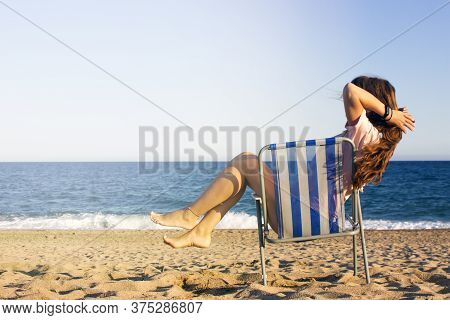 Summer Beach Vacation Concept, Prety Woman With Long Ginger Hair Relaxing And Arm Up On Chair Beach