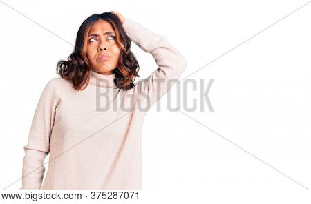 Young beautiful mixed race woman wearing winter turtleneck sweater confuse and wondering about question. uncertain with doubt, thinking with hand on head. pensive concept.