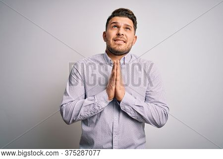 Young business man with blue eyes standing over isolated background begging and praying with hands together with hope expression on face very emotional and worried. Begging.
