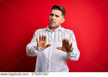 Young business man with blue eyes wearing elegant shirt standing over red isolated background Moving away hands palms showing refusal and denial with afraid and disgusting expression. Stop.