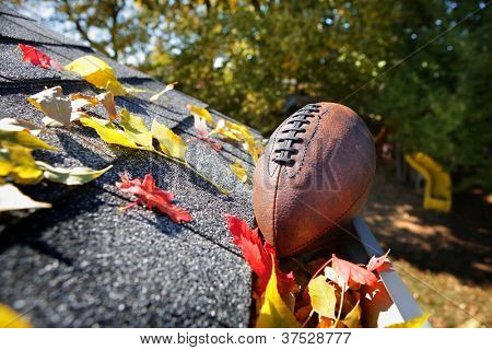 Rain gutter full of autumn leaves with a football poster