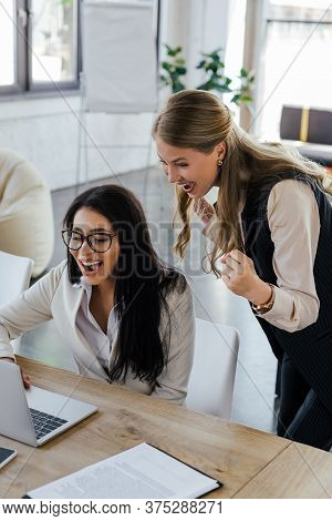 Successful Businesswoman Celebrating Triumph And Looking At Laptop