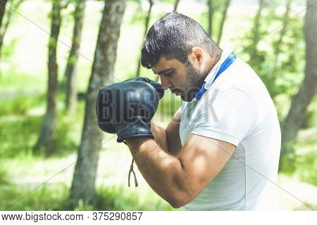 Man Athlete Concentrated Face With Sport Gloves Practicing Boxing Nature Background. Boxer Ready To