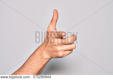 Hand of caucasian young man showing fingers over isolated white background pointing forefinger to the camera, choosing and indicating towards direction