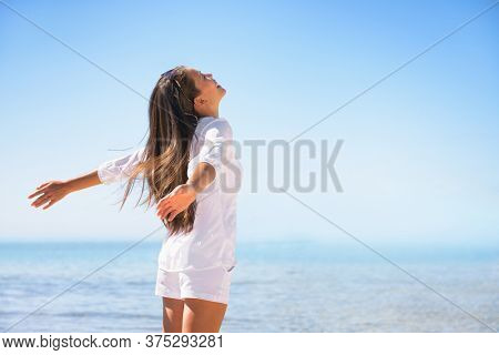 Happy woman happiness emotion feeling free in summer sun lifestyle background. Joy and freedom concept. Asian girl with outstretched arms at beach ocean vacation travel.