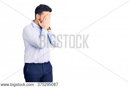 Young hispanic man wearing business clothes with sad expression covering face with hands while crying. depression concept.