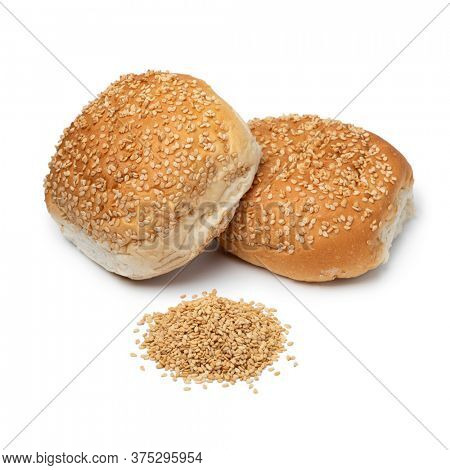 Pair of fresh baked sesame seed buns and a heap of sesame seed isolated on white background