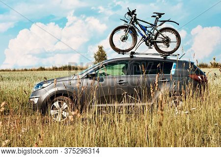 A Car Is Transporting Bicycles With A Mount On The Roof With Two Bicycles Fastened. Summer Vacation