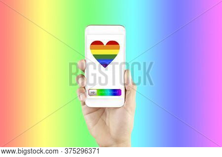 Hand Man Holding Smart Phone In Screen Show Lgbt Symbols. Hand Hold Phone With Rainbow Heart Screen