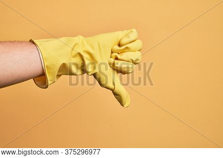 Hand of caucasian young man with cleaning glove over isolated yellow background doing thumbs down rejection gesture, disapproval dislike and negative sign
