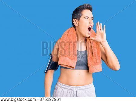 Young woman with short hair wearing sportswear and towel using smartphone shouting and screaming loud to side with hand on mouth. communication concept.