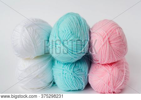 Acrylic Soft Pastel Pink, Azure And White Colored Wool Yarn Thread Skeins Row On White Background, S