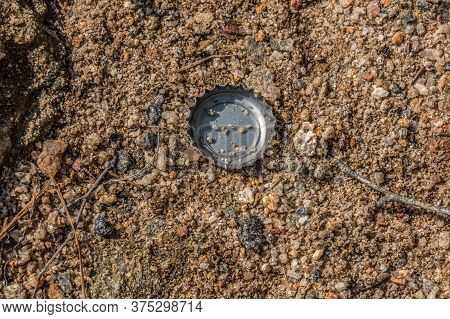 A Single Beer Or Soda Bottle Cap Laying On The Gritty Sand At The Lake On A Sunny Day In Summertime