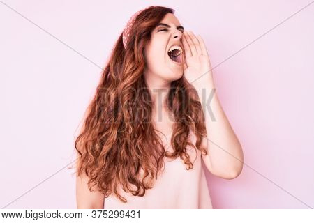 Young beautiful woman wearing casual clothes shouting and screaming loud to side with hand on mouth. communication concept.