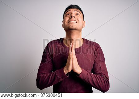 Young handsome hispanic man wearing casual shirt standing over white isolated background begging and praying with hands together with hope expression on face very emotional and worried. Begging.