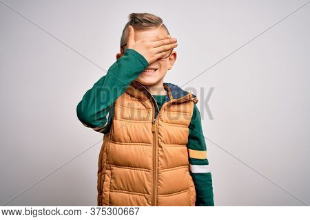 Young little caucasian kid with blue eyes wearing winter coat and smart glasses smiling and laughing with hand on face covering eyes for surprise. Blind concept.