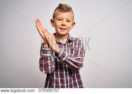 Young little caucasian kid with blue eyes wearing elegant shirt standing over isolated background clapping and applauding happy and joyful, smiling proud hands together