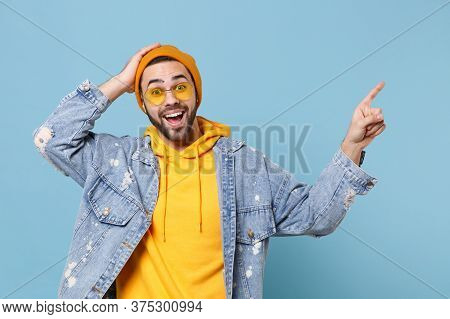 Excited Young Hipster Guy In Fashion Jeans Denim Clothes Posing Isolated On Pastel Blue Background I