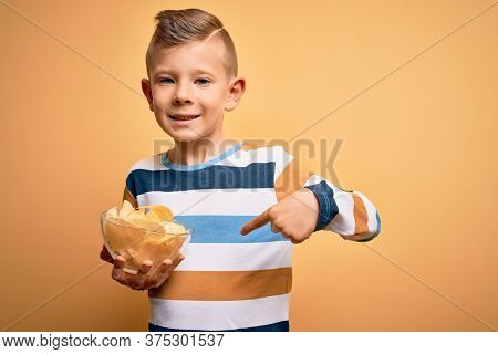 Young little caucasian kid eating unheatlhy potatoes crisps chips over yellow background with surprise face pointing finger to himself