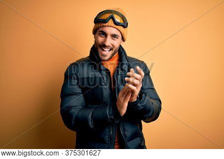 Young handsome skier man with beard wearing snow sportswear and ski goggles clapping and applauding happy and joyful, smiling proud hands together