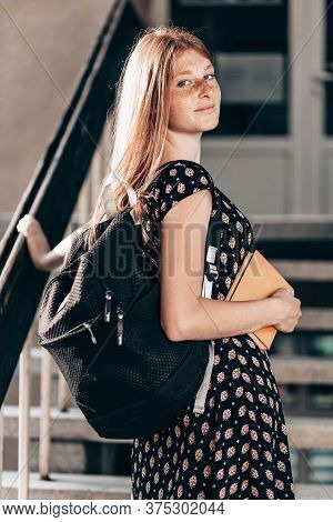 Young, Ginger, Teen School Girl In Front Of Her School, With A Backpack, Looking Happy
