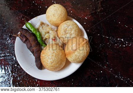 Panipuri Or Golgappa With Spicy Potato Stuff, Tamarind And Chili In A Plate Isolated On Reddish Back