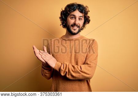 Young handsome man with beard wearing casual sweater standing over yellow background clapping and applauding happy and joyful, smiling proud hands together