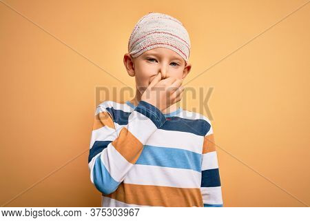 Young little caucasian kid injured wearing medical bandage on head over yellow background smelling something stinky and disgusting, intolerable smell, holding breath with fingers on nose. Bad smell