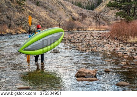 male paddler carrying inflatable whitewater kayak on a shore of mountain river in early spring - Poudre River above Fort Collins, Colorado