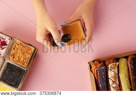Female Hands Holding Dessert In Hands Among Fresh Confectionary