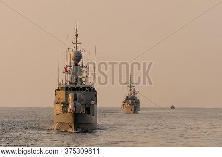 Navy Warship Fleet Underway In Formation In The Sea When Sundown.