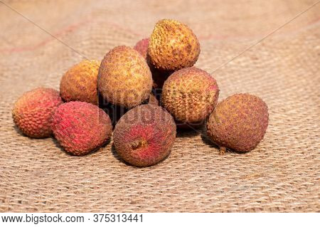 Heap Of Lychee Or Litchi Fruit On Burlap Background