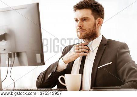 Business concept. Successful young businessman at work. Manager sitting at the office table, working on computer and straightens a tie. Busy man in suit indoors on glass window background.