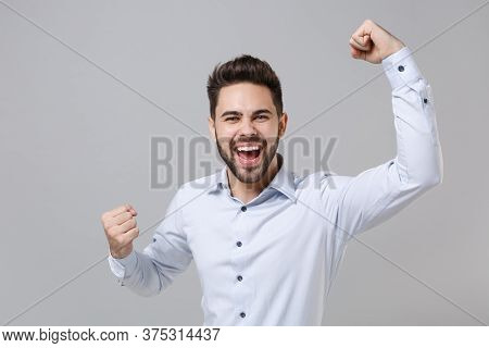 Overjoyed Young Unshaven Business Man In Light Shirt Posing Isolated On Grey Background Studio Portr