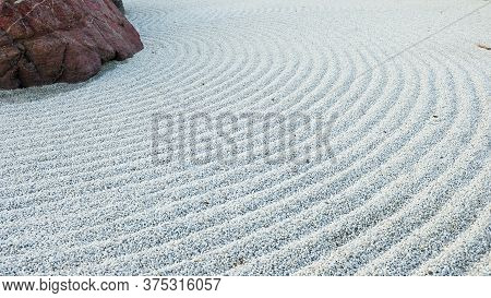 Traditional Details Of Classical Japanese Zen Garden. Volcanic Stones Surrounded Raked Concentric Li