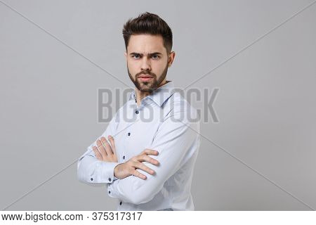 Side View Of Perplexed Young Unshaven Business Man In Light Shirt Posing Isolated On Grey Background