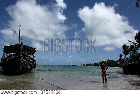 Cairu, Bahia / Brazil - November14, 2013: Fisherman Observes Boat Docked At Second Beach In De Morro