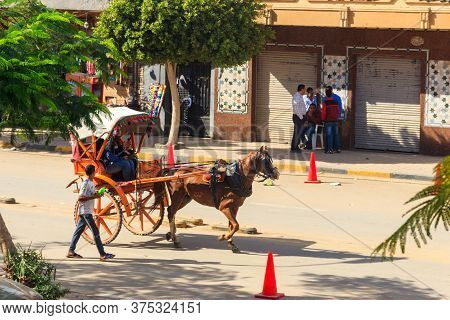 Cairo, Egypt - December 8, 2018: Tourists Riding A Horse Chariot On A Street Of Cairo, Egypt