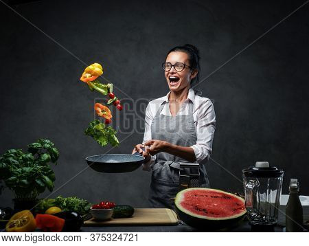 Emotional Mature Female Chef Tossing Chopped Vegetables From A Pan. Healthy Food Concept. Studio Pho