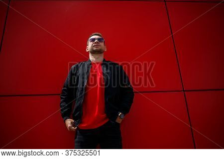 A Cool Young Man In Trendy Sunglasses In A Stylish Red T-shirt With A Black Jacket Stands Near A Red