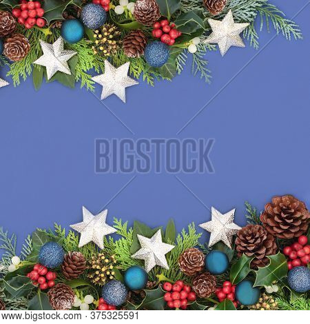 Christmas background border composition with star & blue ball baubles, holly & winter greenery. Xmas composition for the festive season. Flat lay, top view, copy space.