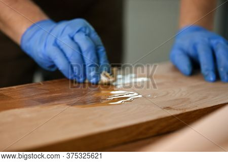 Close-up Of Woodworker Hands In Protective Gloves Covering Wooden Surface. Joiner Lacquering Part Of