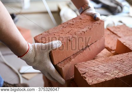 Close-up Of Male Hands Lifting Several Red Bricks At Construction Site. Workman In Protective Gloves
