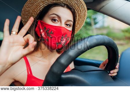Woman Driver Sitting In Car Wearing Protective Mask During Coronavirus Pandemic. Girl Shows Ok Cool