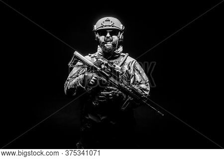 Angry Soldier In Uniform With A Rifle Screaming At Night, Commando In Stress On A Black Background,