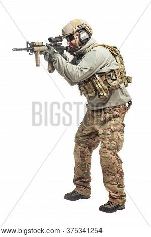 American Soldier In Military Equipment With A Rifle Attacks On A White Background, A Commando With W